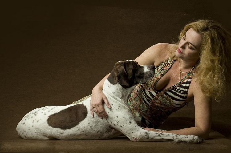 A autora do livro está deitada no chão ao lado de Missy, a cadela