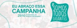 """Logotipo do projeto Somos Todos Gigantes em verde e branco. Ao lado, a mensagem """"Eu abraço essa campanha, 25 de outubro, Dia Nacional da Pessoa com Nanismo"""""""