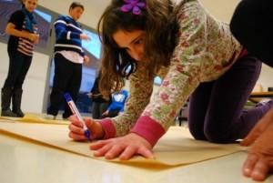 Menina autista está no chão, com uma caneta e uma cartolina, pronta para desenhar ou escrever.