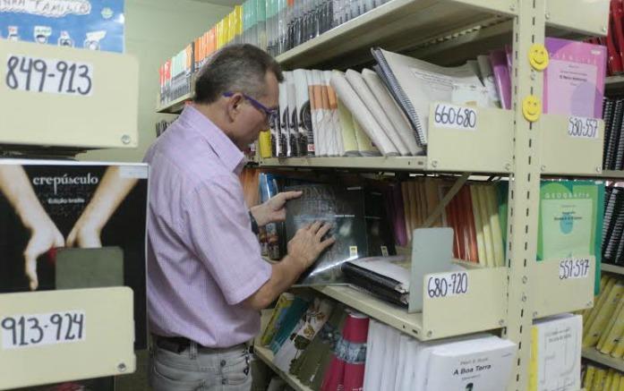 Homem de meia idade está em frente a uma das estantes da blblioteca e toca a capa de um livro com as mãos.