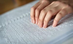 Close em um livro em braile. Uma pessoa utiliza as duas mãos para ler.