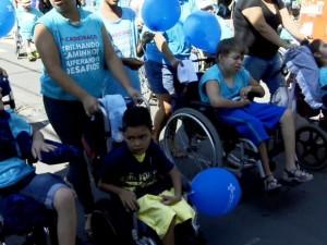 Pessoas protestam em suas cadeiras de rodas, vestindo azul e com balões de aniversário também azuis.