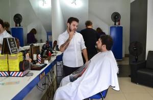 Tiago Rocha em pé no salão, se comunica em Libras com cliente surdo sentado na cadeira para cortar o cabelo