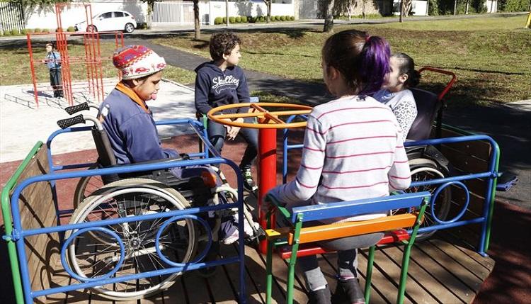 Quatro crianças com idade média de 8 anos brincam em um gira-gira inclusivo; uma delas é cadeirante