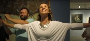 Mulher de braços abertos sorri olhando para cima enquanto um homem toca suas mãos