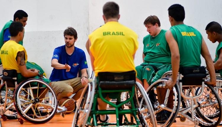 Em círculo, o técnico Tiago Frank em ginásio orienta os atletas de basquete em cadeira de rodas durante treino