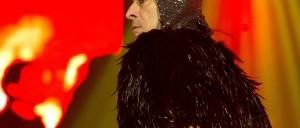 Foto artística de Ney Matogrosso com figurino coberto de penas negras, em um dos shows