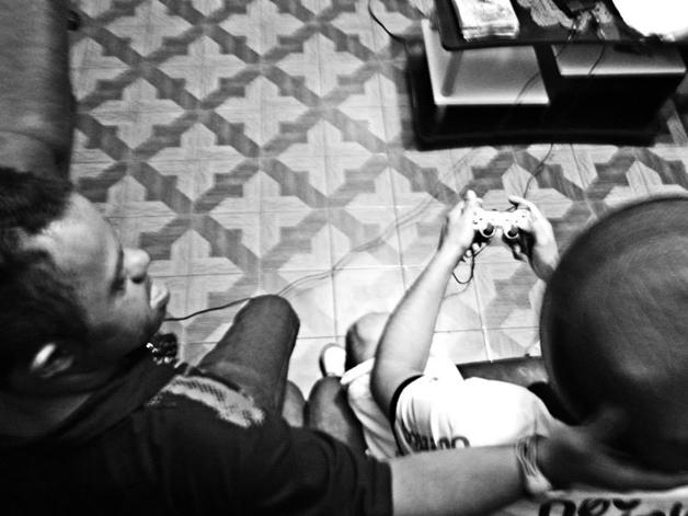Rapaz com deficiência intelectual olha e faz carinho em um amigo sentado ao lado com um controle de videogame nas mãos.