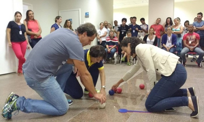 Um homem e duas mulheres estão mexendo com algumas bolinhas que estão pelo chão. Ao fundo, uma plateia acompanha a atividade.