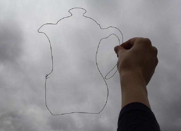 Uma mão tateia o contorno em arame no formato de um bule