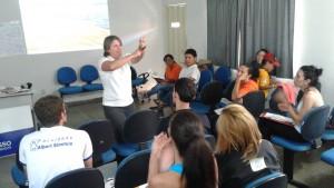 Professora gesticula perante turma de alunos.