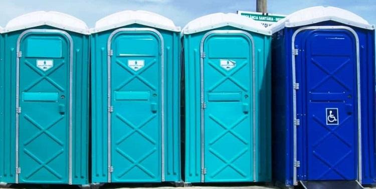 Quatro banheiros químicos em tons de azul dispostos em fileira