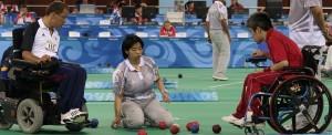 Dois atletas cadeirantes disputam bocha paralímpica, em um ginásio