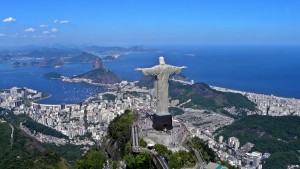 Foto aérea do Rio de Janeiro, com estátua do Cristo Redentor vista de trás e Pão de Açúcar no horizonte
