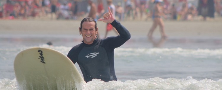 O surfista Cisco Araña em prancha, no mar, com a saudação havaiana de hang loose com as mãos (apenas polegar e mindinho levantados)