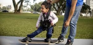 Menino de aproximadamente 6 anos, com deficiência motora, se equilibra em skate adaptado em um parque gramado e com árvores