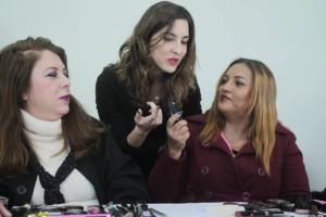 Três mulheres conversando, com produtos de maquiagem nas mãos