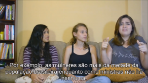 As três alunas estão sentadas lado a lado., enquanto uma delas se comunica em Libras. A legenda fala sobre a falta de representatividade da mulher entre os novos ministros.