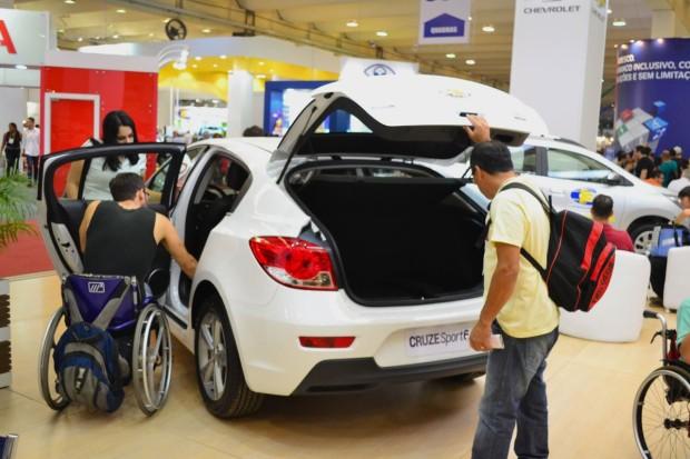 Um homem de amarelo e um rapaz na cadeira de rodas observam um veículo branco adaptado, que está em um estande da Mobility & Show