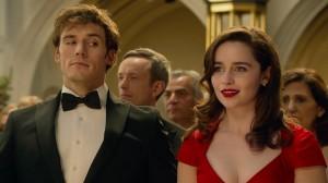"""Cena do filme """"Como eu era antes de você"""". Em um salão de festa, um homem e uma mulher estão vestidos à rigor: o jovem usa smoking, já a moça, um vestido vermelho, os dois têm expressões divertidas e serenas"""