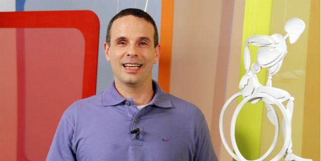 Dudu Braga está em um cenário de TV, usando camisa roxa e sorrindo.