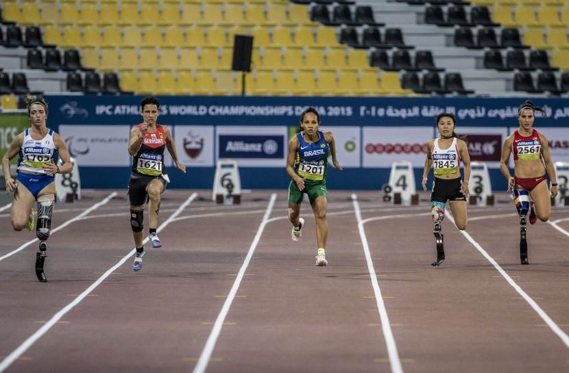 Cinco atletas paralímpicas vistas de frente disputam prova de velocidade.