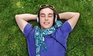 Rapaz está deitado de costas na grama, com as mãos atrás da cabeça. Com os olhos fechados, ele usa fones de ouvido e sorri.