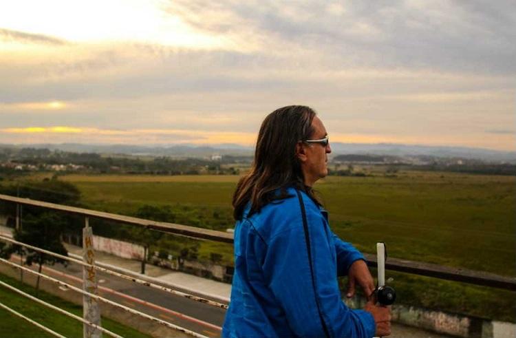 Homem de óculos escuros e bengala contempla o horizonte