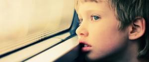 Close no rosto de uma criança, que olha distraidamente por uma janela.