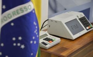 Urna eletrônica mostra, na tela, a palavra FIM, indicando o fim da votação. Ao lado esquerdo, em primeiro plano e desfocada, está a bandeira do Brasil.