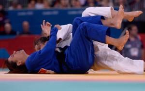 Duas judocas estão deitadas no tatame, lutando. Uma usa kimono azul, e a outra usa kimono branco.