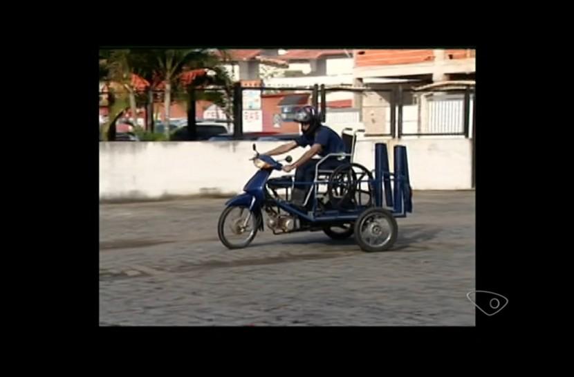 Rapaz pilota a moto adaptada. Ela possui três rodas, como um triciclo, com espaço para a cadeira de rodas.