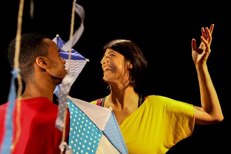 Foto de um espetáculo de dança; uma jovem mulher, com uma blusa amarela, sorri com os braços arqueados, enquanto um outro homem interage com ela; há pedaços coloridos de tecido descendo do teto