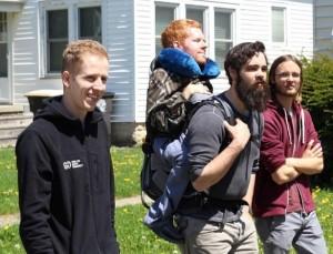 Foto de três jovens, com barba e mochilas, com um outro jovem nas costas, carregado como se fosse uma mochila
