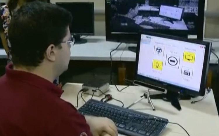 Um homem jovem sentado em frente a um computador, acessando-o sem o uso de teclado ou mouse
