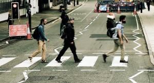Foto de três jovens atravessando a rua Abbey Road, com um rapaz menor carregado nas costas de um deles
