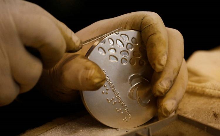Foto de mãos com luvas cirúrgicas manuseando a medalha paralímpica durante a produção