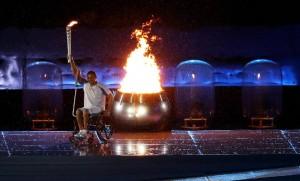 Clodoaldo Silva, nadador paralímpico brasileiro, está em sua cadeira de rodas, com e segura a tocha ao lado da pira olímpica acesa. Ele foi o responsável por acender a pira durante a abertura dos jogos.