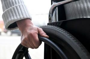 Uma mão masculina segura as rodas de uma cadeira de rodas
