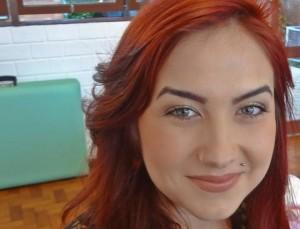 Foto de uma jovem branca com longos cabelos avermelhados e olhos claros; ela olha na direção da câmera e sorri