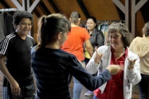 Em uma sala fechada, várias pessoas jovens estão em duplas, em um exercício de teatro. Uma jovem com Síndrome de Down sorri olhando na direção de outra jovem, durante o exercício
