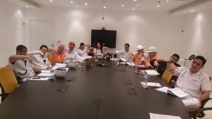 Em uma sala de reunião, várias pessoas estão sentadas próximas as outras, fazendo símbolos em libras