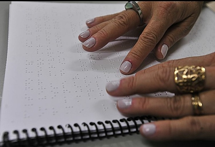 Duas mãos femininas, com esmalte em tons claros e anéis nos dedos tateiam um livro em braile