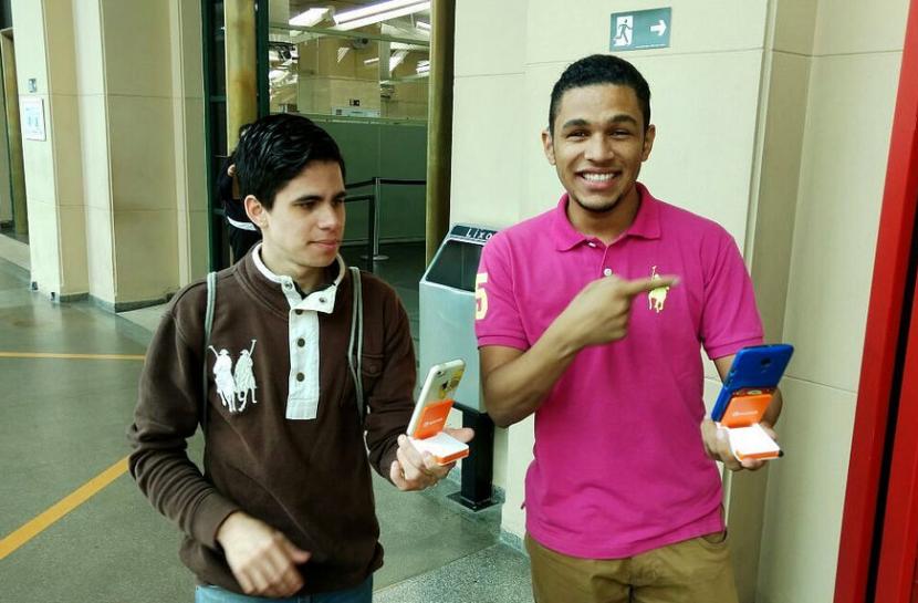 Dois rapazes sorriem com seus celulares nas mãos.