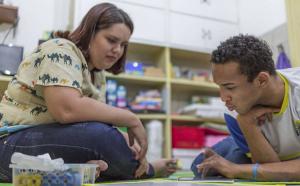 Em uma biblioteca escolar, uma jovem professora, de cabelos curtos, acompanha um aluno mais velho, com deficiência, observando um tablet