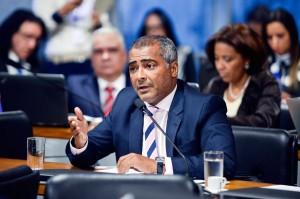 Foto do senado, com diversos políticos sentados ao fundo; o destaque é senador Romário, autor do projeto. Ele usa um terno azul, camisa rosa e uma gravata listrada em azul e rosa e está sentado, falando em um microfone.