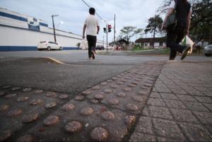 Foto de uma calçada com piso tátil; um jovem homem, de costas, está caminhando