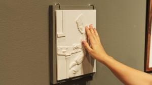 Foto de uma obra em alto relevo sendo tateada por uma mão feminina; a imagem tátil é de um senhor sentado em frente a uma mesa