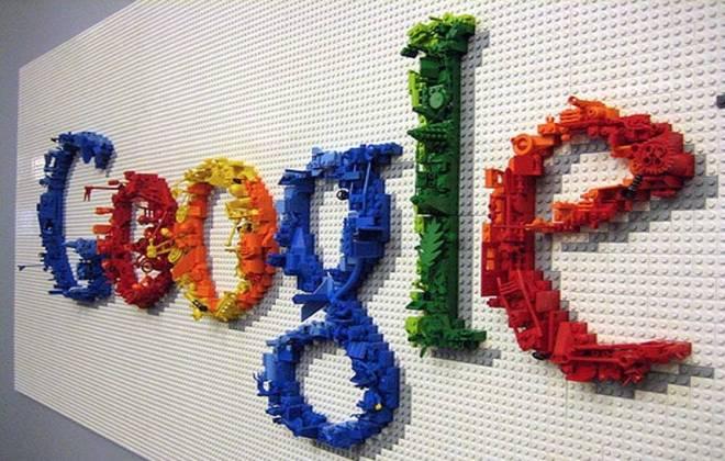 Foto de um painel de Legos do tamanho de uma parede, com o logotipo formando a palavra Google com peças de lego nas cores azul, vermelho, verde e amarelo