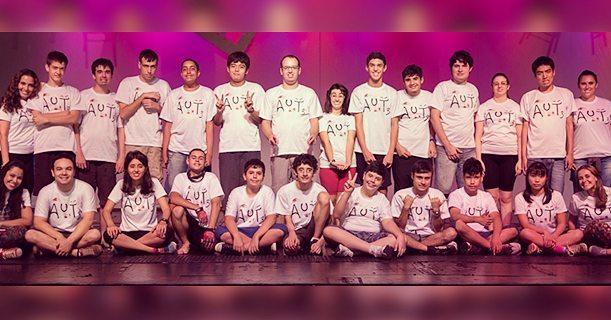 Em um palco de teatro, os atores com espectro autista posam para a foto, disposto lado a lado e sentados no chão